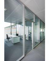 Blick durch das transparente Büro auf das Bestandsgebäude