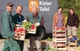 Björn Kluvetasch und Volker Tiedemann übergeben die Ernte an Holger Hocker von der Kieler Tafel