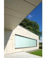 Die transluzente Glaskonstruktion stellt einen farblichen Kontrast zur Fassade dar.