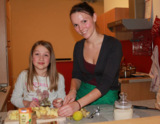 Linn (8) schneidet Äpfel mit angehender Ernährungswissenschaftlerin Eva Bayer (24). Foto: M. Dietl.