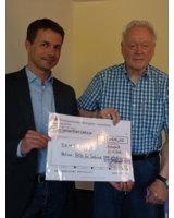Jens Göhner überreicht der Kirchengemeinde den Spendenscheck von Willi DAMM