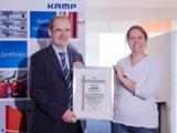 Herr Lante und Frau Knorr halten die Bescheinigung in einem Bilderrahmen in der Hand.